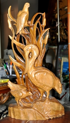 Carved wooden sculpture of stork and other birds in a grassland