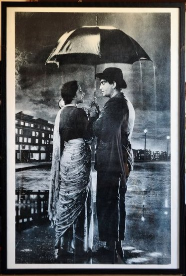 Poster of Nargis and Raj Kapoor standing under an umbrella in monsoon rain singing Pyar hua ikrar hua in the 1955 film Shree 420​