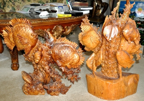 Wood carved sculptures of fish swimming in the ocean