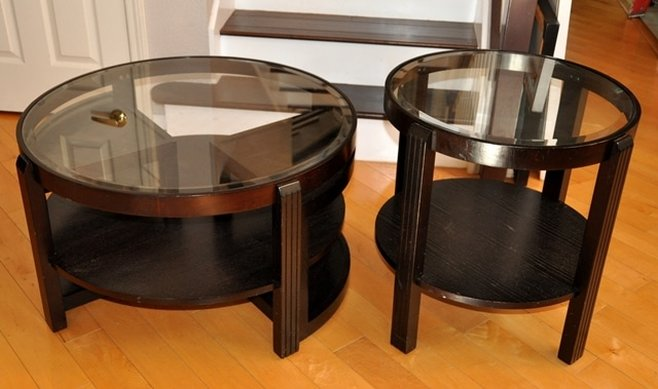 Pair of circular wooden coffee and end tables with beveled glass tops