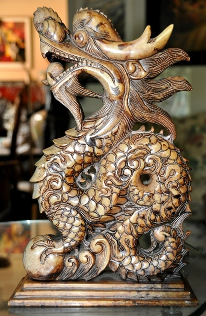 Marble sculpture of a dragon holding pearls in its paw and mouth