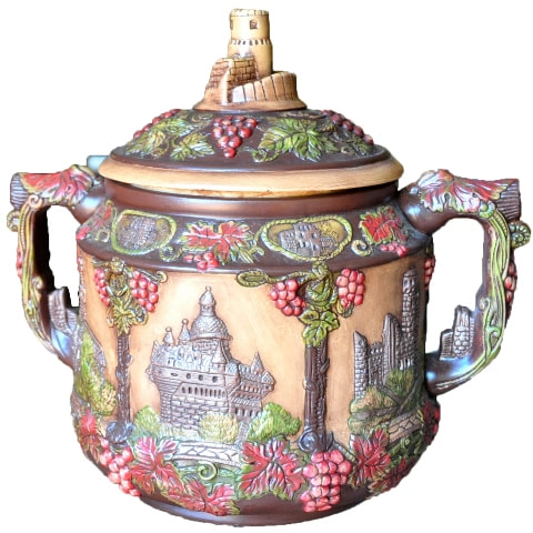 Vintage German pottery cookie jar with relief features depicting castles