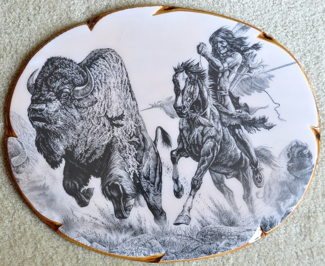 This is an etching by Montana artist Bill O'Neill titled Buffalo Hunt which shows a Native American on horse chasing a bison (buffalo).  It is mounted and laminated on an oval wood board of 19