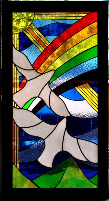 Large stained glass window with flying birds, rainbow and sun