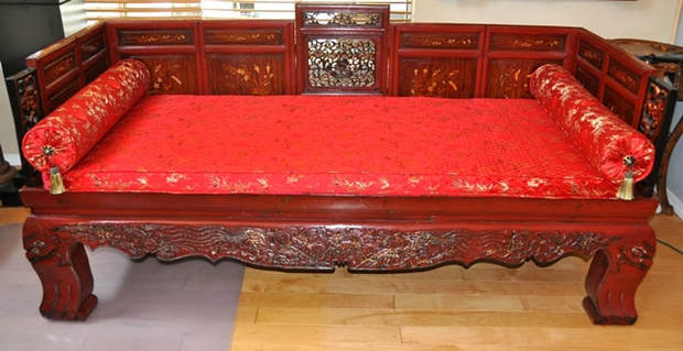 Late Qing Dynasty gilt decorated red lacquered opium bed with wood and ivory inlaid panels