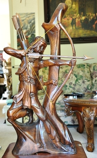 Wood carved sculpture of a Native American shooting an arrow from his bow