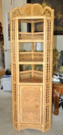 Wicker and wood corner stand of unique design with multiple shelves and a cabinet