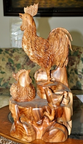 Wooden sculpture of a chicken family of a rooster, a hen and 3 chicks