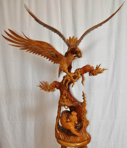 Large wooden sculpture of two eagles on top of a tree and a lion at the bottom