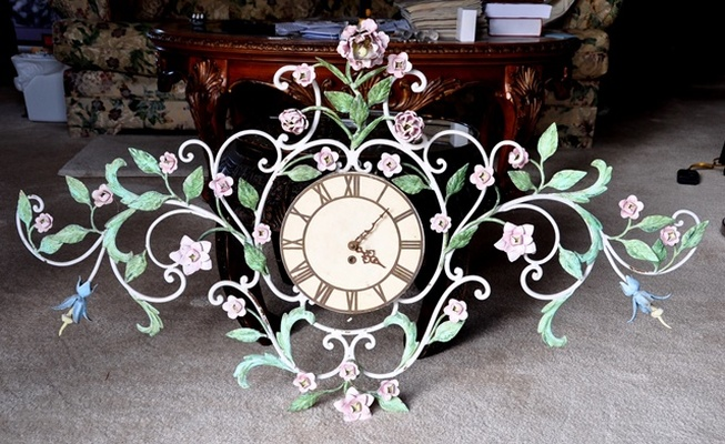Antique ornate clock with a metal frame of vines, flowers and leaves