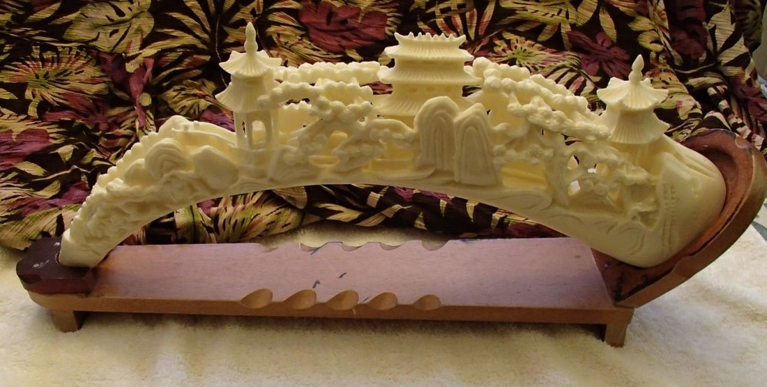 17 inchj long faux ivory carving of Oriental village on resin tusk