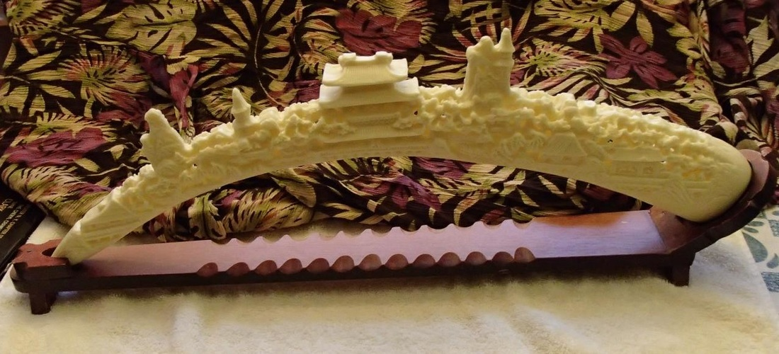 23 inch long faux ivory carving of Oriental village on resin tusk