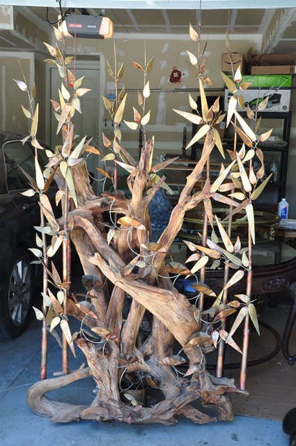 Brutalist copper bamboo groove sculpture on driftwood water fountain