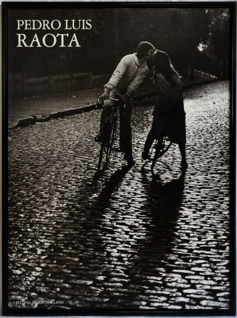 Poster of photograph by Pedro Luis Raota depicting a couple kissing while straddled on their bicycles