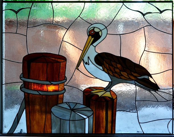 Stained glass window showing a pelican sitting on a tree stump