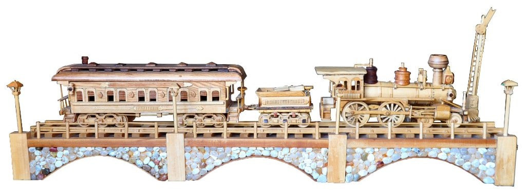 Large wooden replica of the Iron Horse train with steam locomotive and wagon crossing a stone bridge