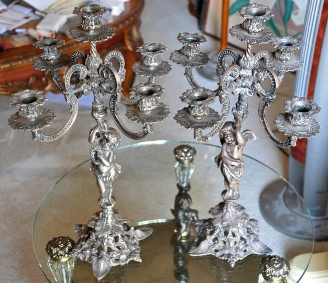 Pair of ornate metal candelabra with figural bases
