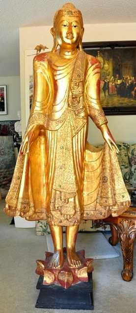 Large wooden standing Thai Buddha statue covered in gold leaf