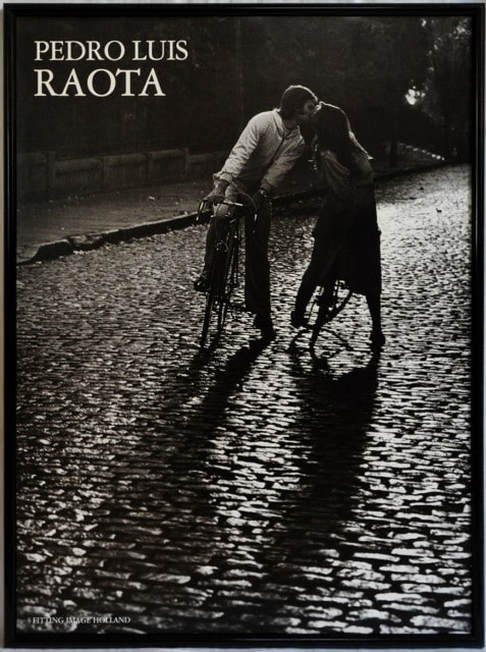 Poster of photograph by Pedro Luis Raota of a couple kissing while straddled on their bicycles